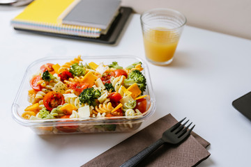Healthy food in lunch box, on working table with laptop