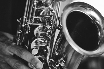 Black and white closeup picture of hands of a man playing saxophone