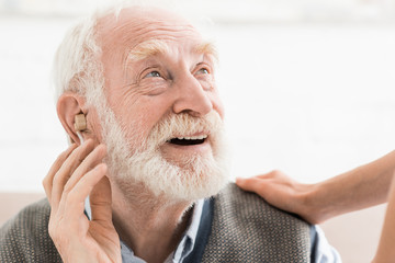 Glad man with hearing aid in ear, looking away