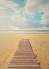 vacation background of beach with wooden boardwalk on summer
