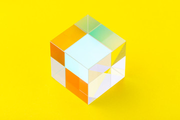 Colorful bright glass cube on yellow background, abstraction, minimalism