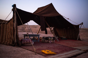 Berber tent in the Sahara desert in Morocco, Africa. This is the traditional home for Berbers and desert travelers. Behind the mountains the sun is setting.