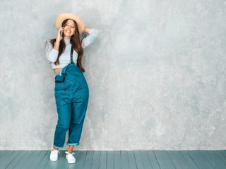 Young beautiful woman speaking on phone. Trendy girl in casual summer overalls clothes and hat. Funny and positive female posing near gray wall in studio Wall mural