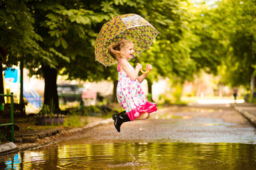 Happy funny kid girl with umbrella jumping on puddles in rubber boots and in polka dot dress and laughing