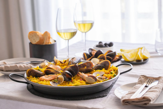 Seafood Paella with  prawns, clams, mussels on saffron rice and vegetables and  bottle of white wine on restaurant table.