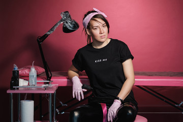 Portrait of a professional tattoo master woman. Black clothes, and dreadlocks. Red, pink and white background. Place of work tattoo master.