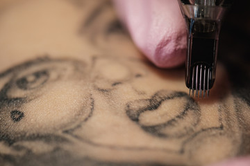 Close-up of a tattoo needle. The process of the tattoo master. Pink women's protective gloves.