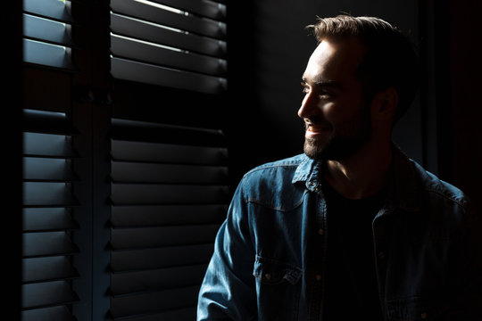 Silhouette of young smiling man standing in dark room at shadow blinds