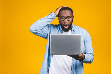 Young surprised african man standing and using laptop computer isolated over yellow background.
