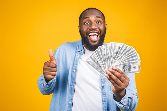 Winner! Young rich african american man in casual t-shirt holding money dollar bills with surprise isolated over yellow wall. Thumbs up.