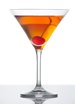 Manhattan drink with red cherry on white