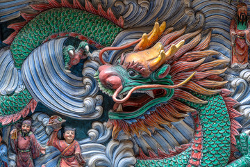 Detail of a dragon statue on a wall in a Chinese temple in Singapore, closeup