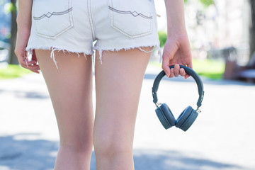 Back rear behind closeup cropped view photo of slim fit shape slender attractive lady's hips dressed up in mini shorts holding portable portative gray without wire head-phones