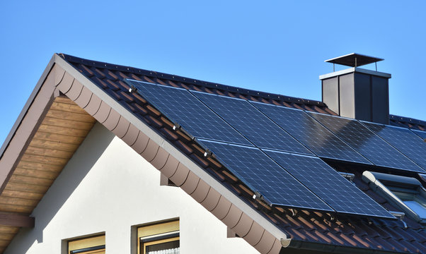 Solar panels installed on the roof of a house with tiles in Europe against the background of a blue sky. Green technology