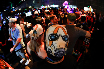 Attendees wearing masks from the Borderlands 3 game wait in line at E3, the annual video games expo experience the latest in gaming software and hardware in Los Angeles
