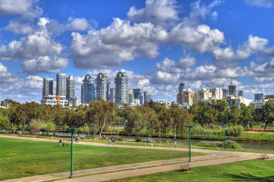 Beautiful HDR image of the skyline of the center-north of Tel Aviv with the Yarkon River on dramatic blue and cloudy sky