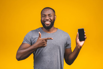 Portrait of a smiling young afro american man dressed in casual isolated, pointing at blank screen mobile phone.
