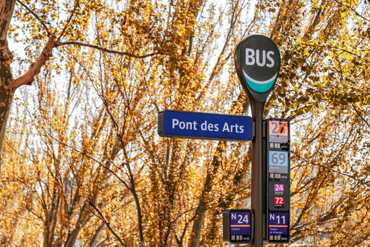 Ponts des Arts (Bridge of Arts) bus stop sign in Paris, France. Yellow leaves tree in autumn.