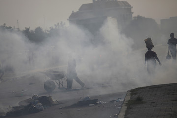 People walk amid the smoke of a barricade made with garbage in a blocked street during a strike day in Port-au-Prince