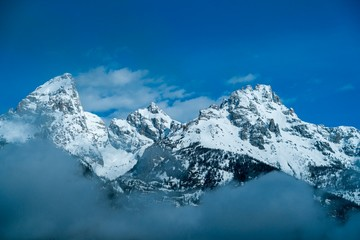 Snow-covered rocky mountain peaks surrounded by misty clouds