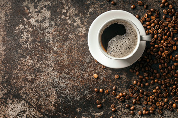 Wall Mural - Coffee cup and coffee beans on dark stone background. .