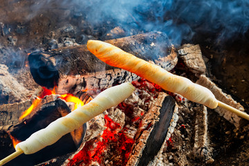 Barbecue with fresh bread on wooden sticks, Stockbrot (stick bread). Fototapete