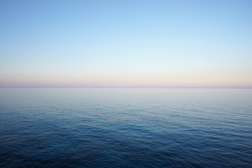 Seascape in delicate pastel colors with the horizon of the sea and clear sky early in the morning. Mediterranean Sea