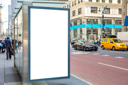 Blank billboard at bus stop for advertising, New York city buildings and street background