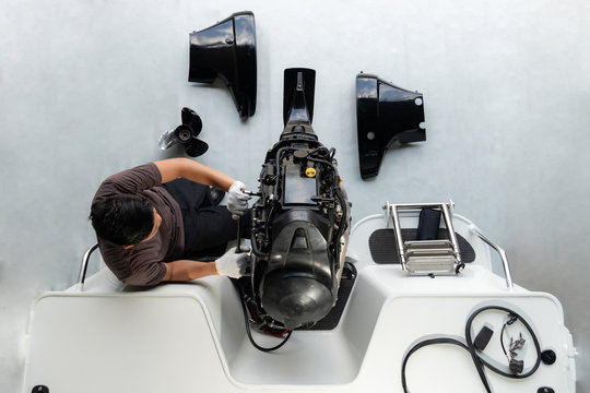 Repairing engines on aluminum boats , The technician is removing the boat parts to make the paint