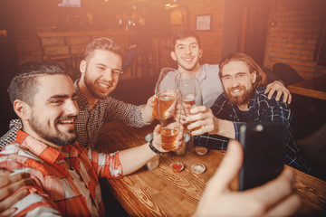 Male friends make selfie photo on phone with glasses of beer bar pub. Concept of friendship