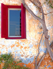 Athens Greece, red shutters window and plant on colorful ocher wall in anafiotika picturesque neighborhood under acropolis