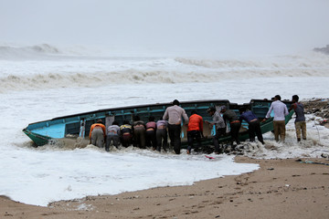Fishermen move a fishing boat to a safer place along the shore ahead of Cyclone Vayu in Veraval