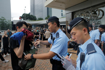A police officer checks the bag of a pedestrian following a day of violence in Hong Kong