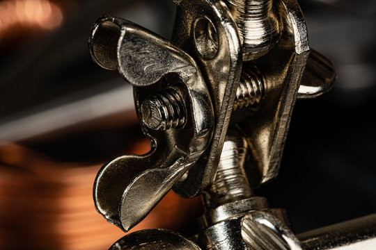 A wing nut and thumb screw securing a steel ball joint on a pice of shop equipment.