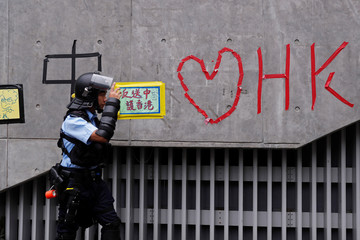A riot police officer walks past a wall covered with messages following a day of violence over an extradition bill, in Hong Kong