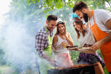 Friends making barbecue and having lunch in the nature Wall mural