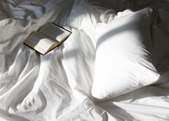 Creative photo composition with book and white bed under the sun light from window