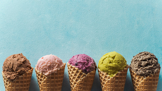 Various ice cream scoops in cones with copy space. Colorful ice cream in cones chocolate, strawberry, blueberry, pistachio or matcha, biscuits chocolate sandwich cookies on blue background. Top view