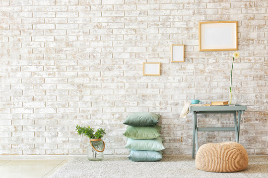 Table, pouf and soft pillows near brick wall