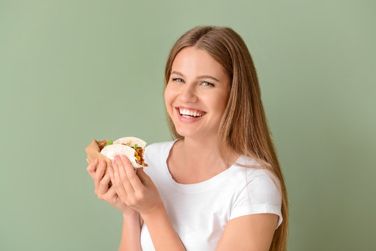 Woman eating tasty taco on color background