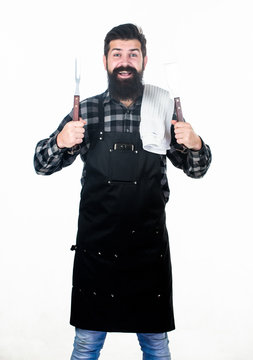 Cooking meat in park. Barbecue master. Bearded hipster wear apron for barbecue. Roasting and grilling food. Man hold cooking utensils barbecue. Tools for roasting meat outdoors. Picnic and barbecue