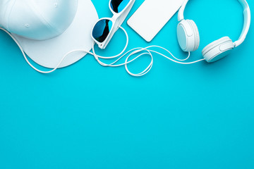 Flat lay image of modern teenager accessories background - headphones, sunglasses, smartphone, baseball cap. Top view of white accessories on turquoise blue background with copy space