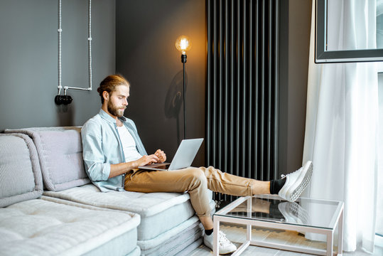 Man working with laptop while sitting on the couch in the living room at home