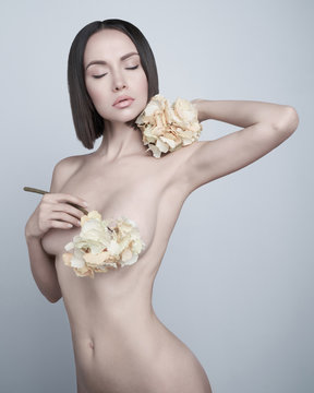 Fashion art photo of elegant nude model with the summer flowers