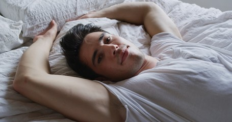 Authentic shot of young handsome man is relaxing in the bedroom in the early morning in a sunny day.