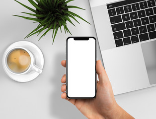 Smartphone frameless in hand blank screen on business desk - laptop, coffee, grass, flower background