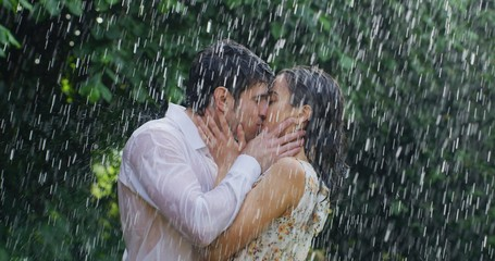 Portrait of young carefree couple in love are hugging and kissing under the rain on a background of green trees.