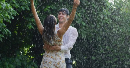 Portrait of young carefree couple in love are dancing and kissing under the rain on a background of green trees.