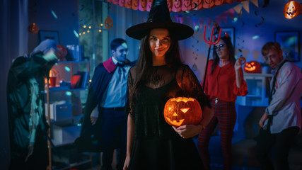 Halloween Costume Party: Gorgeous Seductive Witch Wearing Dress Holds Burning Pumpkin. Background: Beautiful Devil, Scary Death, Count Dracula, Zombie Dancing in the Decorated Room Fototapete