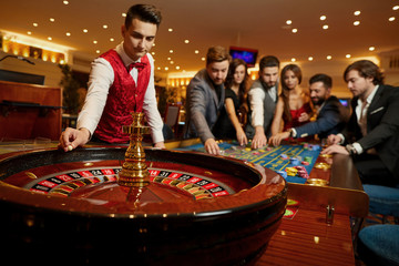 Fototapeta The croupier holds a roulette ball in a casino in his hand.